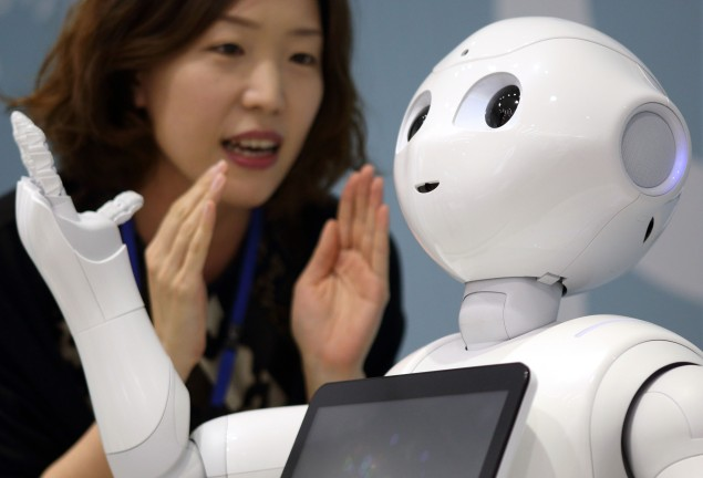 Typical Image of Japan and Technology (nope no sign on an VCR player here) A woman interacts with the humanoid robot Pepper, developed by SoftBank Corp.'s Aldebaran Robotics SA unit, at a SoftBank store in Tokyo, Japan.